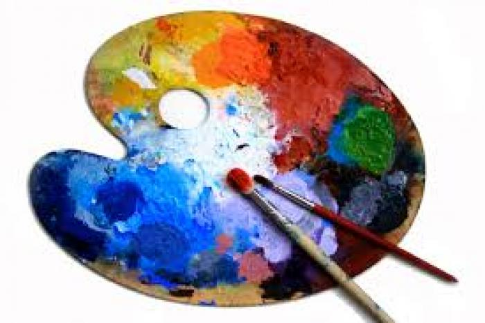 a painters palette covered in paint of all colours